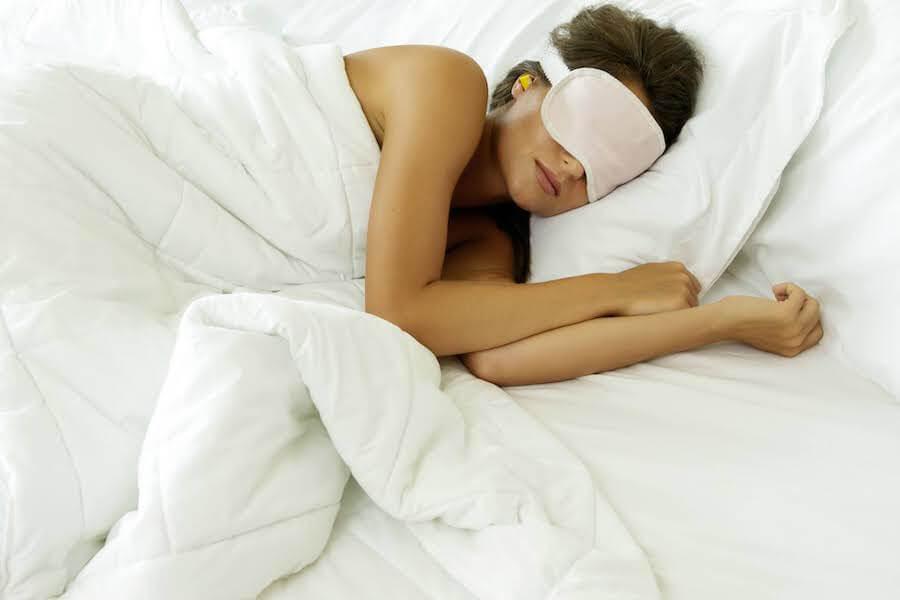 Girl sleeping with eyemask on, and ear plugs